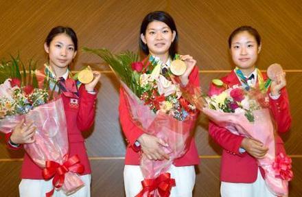 花束を手に記念写真に納まるバドミントン女子ダブルスの松友美佐紀(左)、高橋礼華(中央)、同シングルスの奥原希望の各選手=25日午後、東京都内(共同)